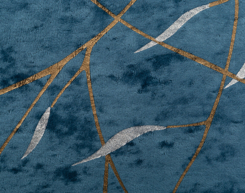Close-up of Charisma Duvet Cover's golden branch pattern on blue.