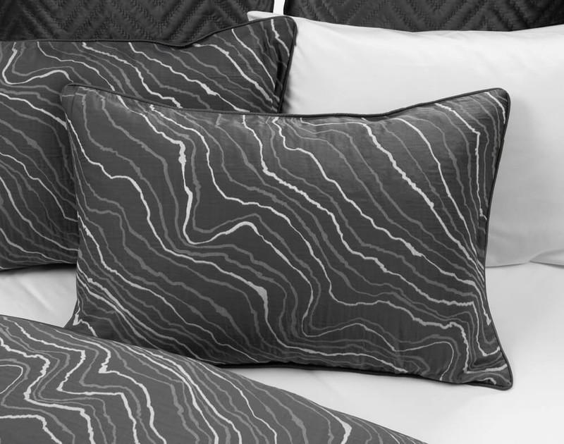 Palisade Black Pillow Shams resting on half-open bedding.