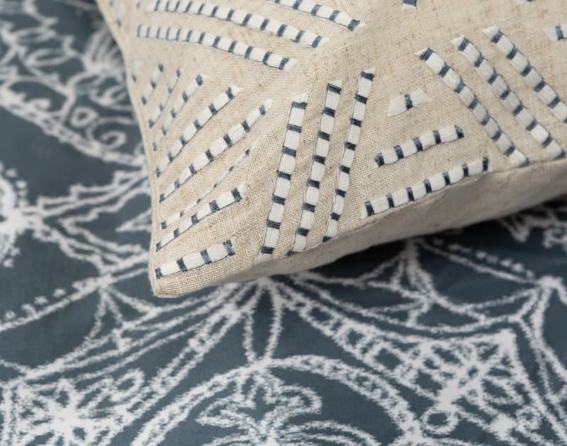 Sonesta Square Cushion Cover detailing displaying the blue and white pick stitch on a creamy beige background