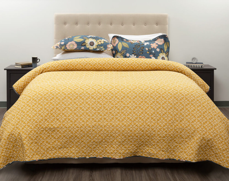 Reverse side of the Amita Cotton Quilt Set styled over a bed.