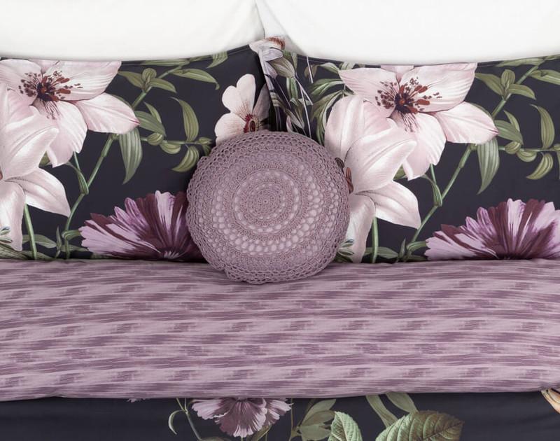 Greta Round Cushion Cover laying on Greta Pillow Shams and Greta Duvet Cover's reverse.