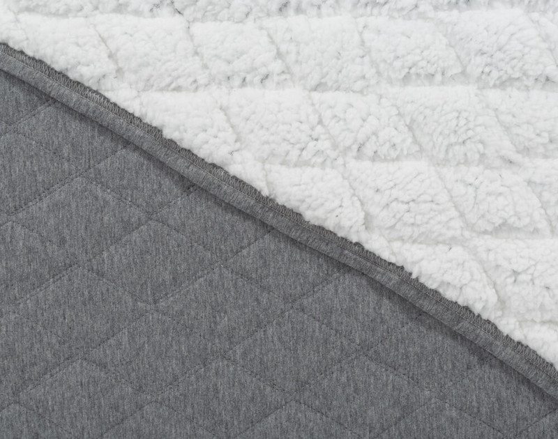 Close-up of our the front surface and white fluffy interior of our Chevron Jersey Quilt Set.