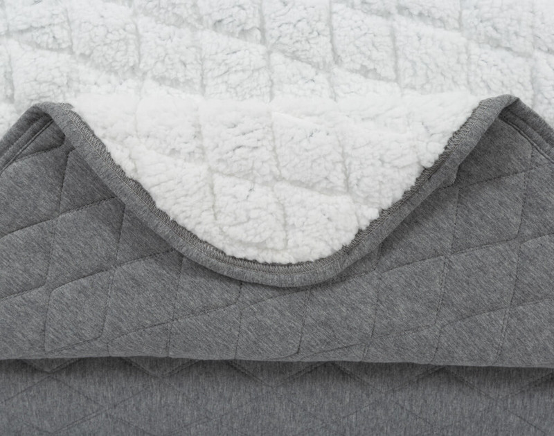 Folded corner of our Chevron Jersey Quilt Set to show white interior and grey exterior, as well as smooth curved corners.