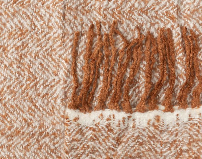 Close-up of the frayed fringe edges and herringbone fabric of our Copper Herringbone Knit Fringe Throw.