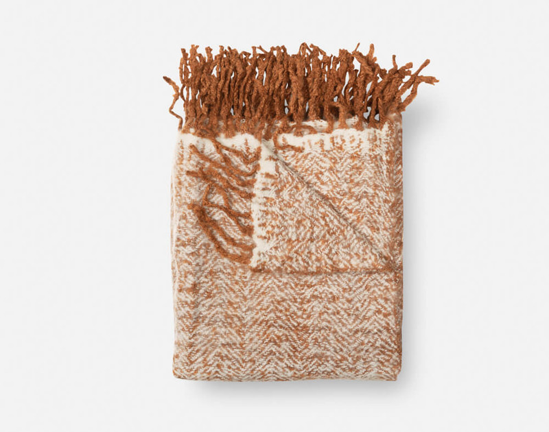 Our Copper Herringbone Knit Fringe Throw folded into a square.