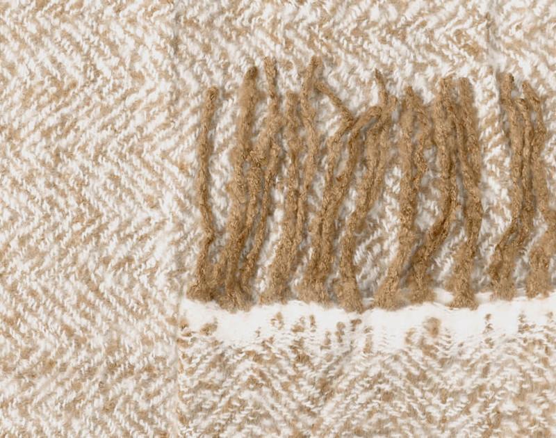 Close-up of the frayed fringe edges and herringbone fabric of our Oat Mix Herringbone Knit Fringe Throw.