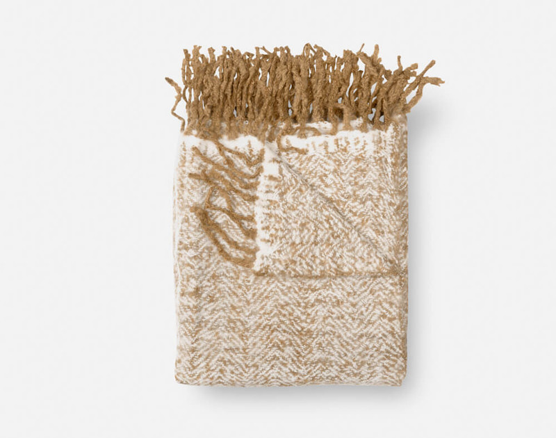 Our Oat Mix Herringbone Knit Fringe Throw folded into a square.