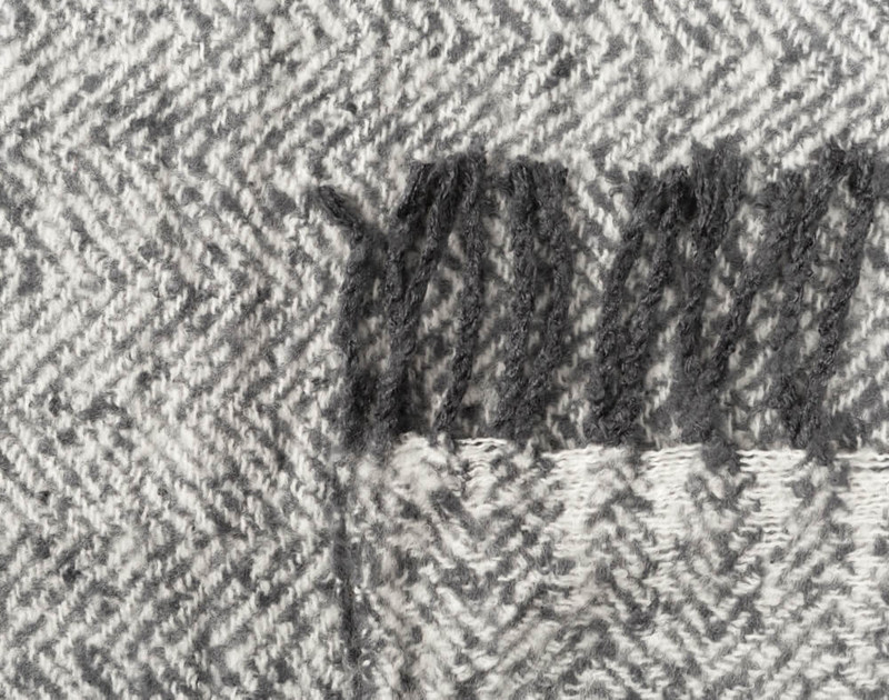 Close-up of the frayed fringe edges and herringbone fabric of our Grey Mix Herringbone Knit Fringe Throw.