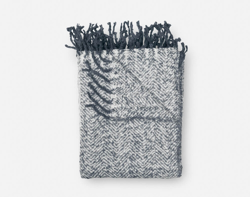 Our Grey Mix Herringbone Knit Fringe Throw folded into a square.