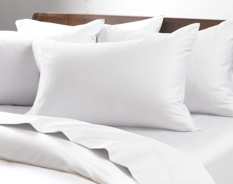 Pillows on a bed fitted with Cotton Blend Percale Pillowcases.