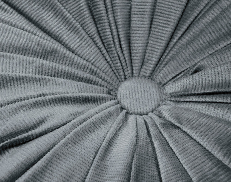 Close-up of the button center and folded fabric of our Charcoal Round Corduroy Cushion.