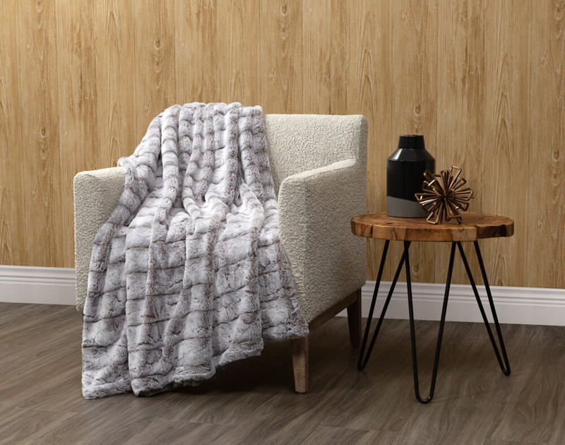 Tip-Dyed Faux Fur Throw in Silver draped over a living room chair.