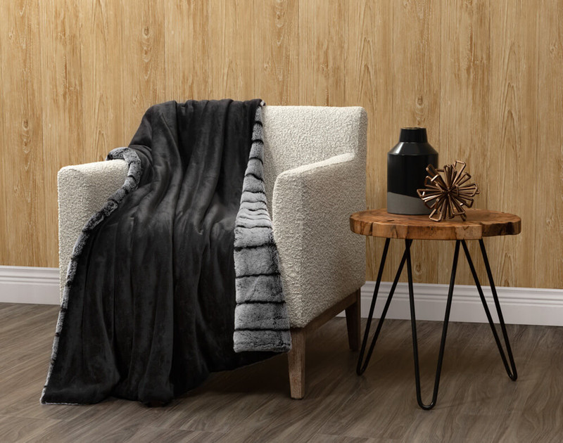 Reverse of Tip-Dyed Faux Fur Throw in Black draped over a living room chair.