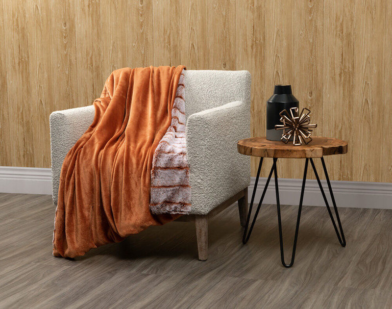 Reverse of Tip-Dyed Faux Fur Throw in Copper draped over a living room chair.