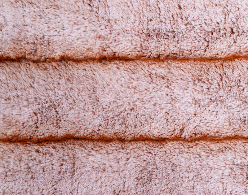 Front side of Tip-Dyed Faux Fur Throw Copper with ribbed fabric stripes and beige undertones.