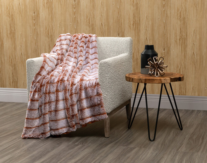 Tip-Dyed Faux Fur Throw in Copper draped over a living room chair.