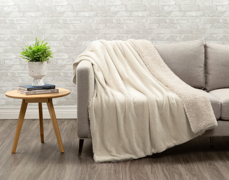 Lambswool Faux Fur Throw in Natural draped over a living room couch.