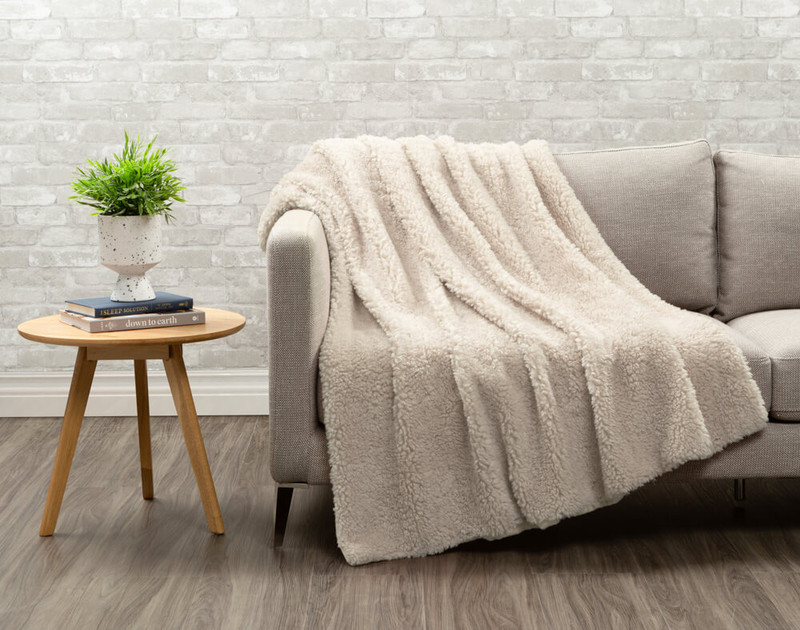 Sherpa side of Lambswool Faux Fur Throw in Natural draped over a living room chair.