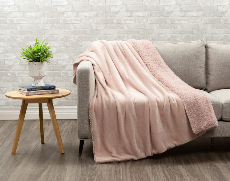 Lambswool Faux Fur Throw in Blush draped over a living room couch.