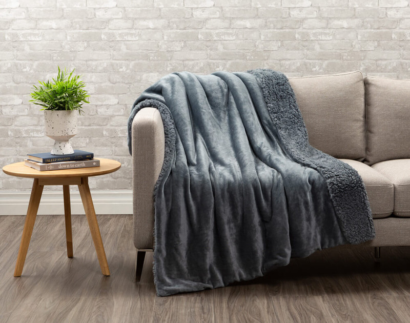 Lambswool Faux Fur Throw in Thundercloud draped over a living room couch.