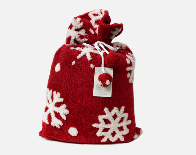 Our Red Holiday Sherpa Throw in Sugar Snow stowed in its comfortable fabric pouch.