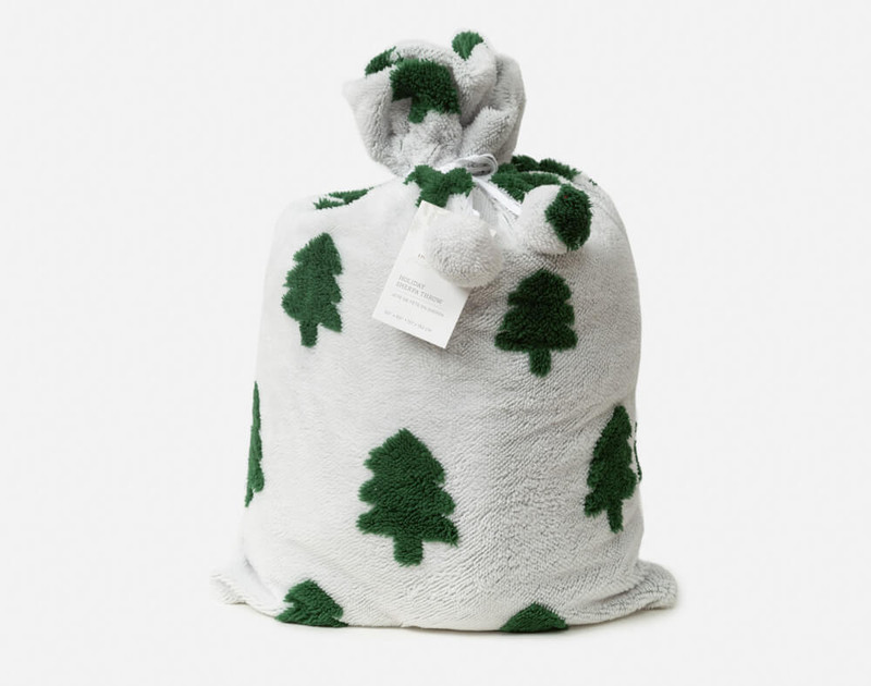 Our White and Green Holiday Sherpa Throw in Tree Time stowed in its comfortable fabric pouch.