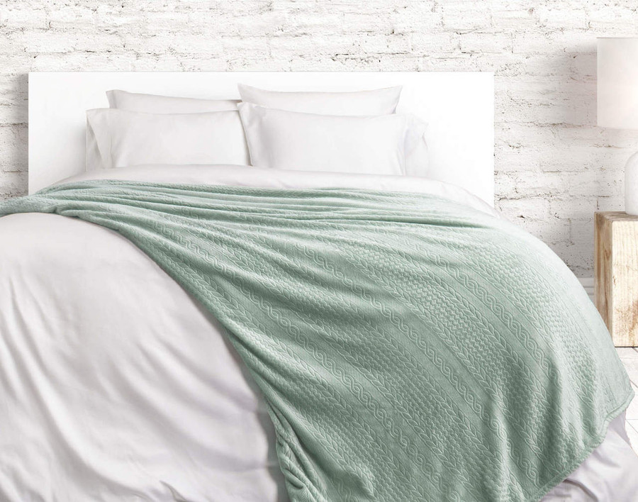 The Cable Knit Blanket in Seafoam, a light mint green.