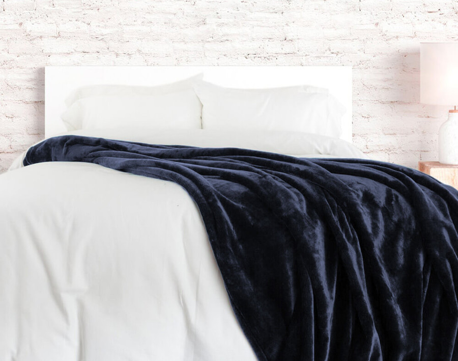 The Cashmere Touch Fleece Blanket pictured in Navy, a rich dark blue.