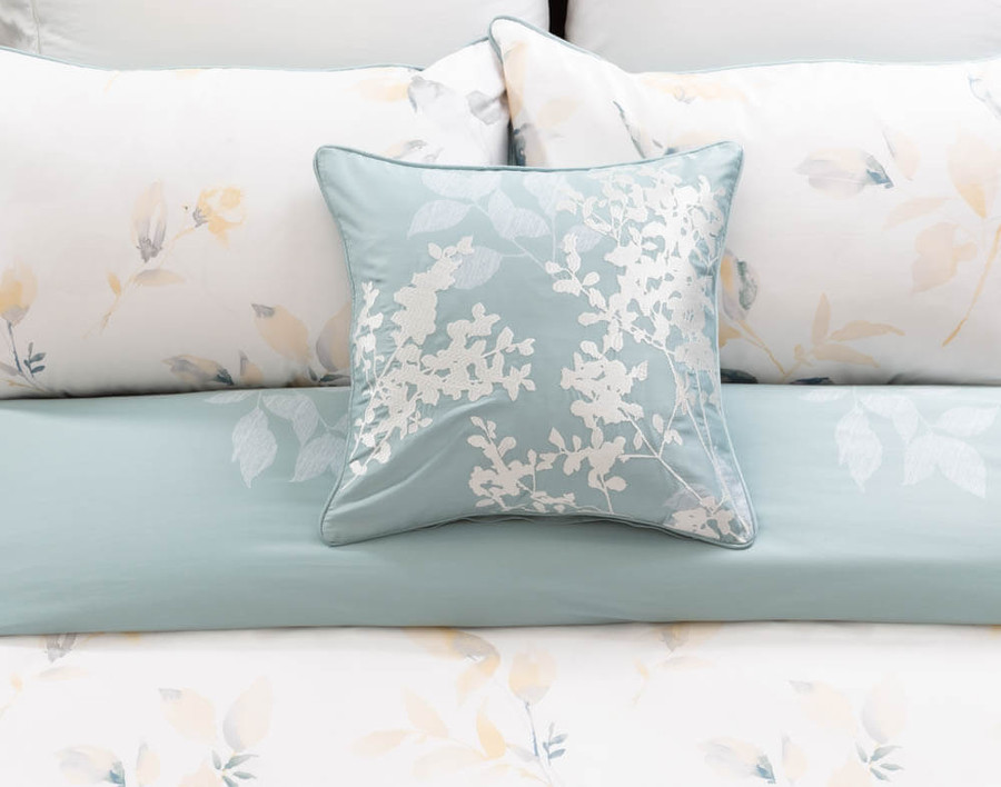 Repose Square Cushion Cover in soft aqua with white leaves on bed.