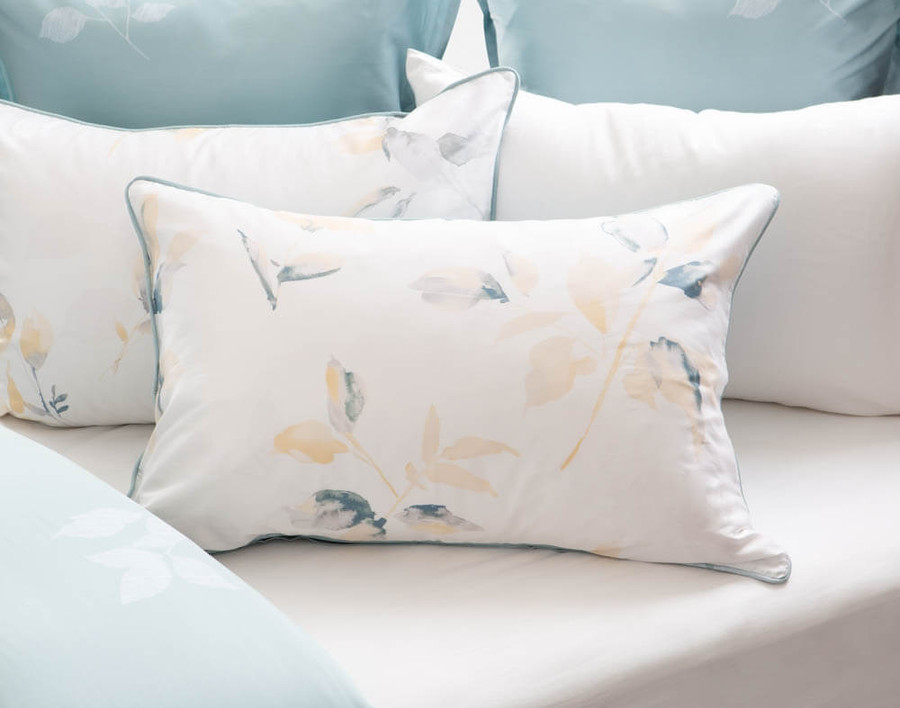 Repose Pillow Sham featuring teal and yellow leaves on a white background on a bed.