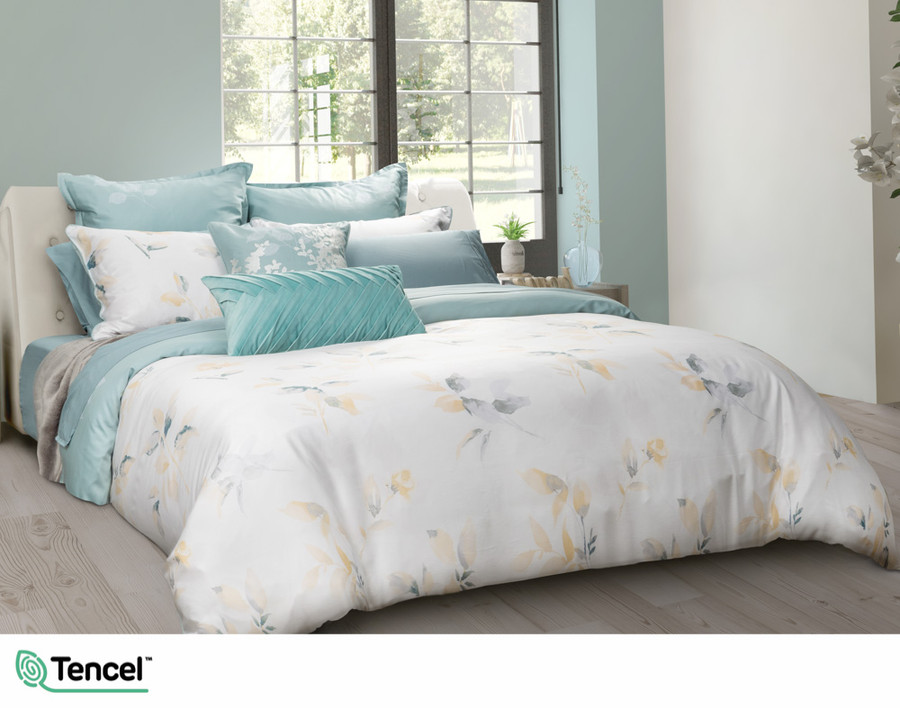 Repose Duvet Cover featuring teal and yellow leaves on a white background in a teal bedroom.