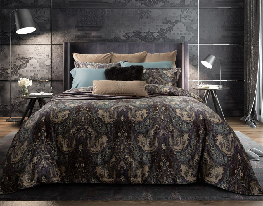 Tristan Duvet Cover features shades of brown, purple, and teal in a classic paisley print that reverses to a tan quatrefoil pattern, shown with our Tidewater sheeting.