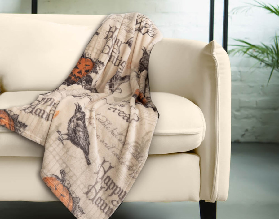 Haunting Halloween Fleece Throw features jack o' lanterns, black ravens, and gothic script on a cream background.