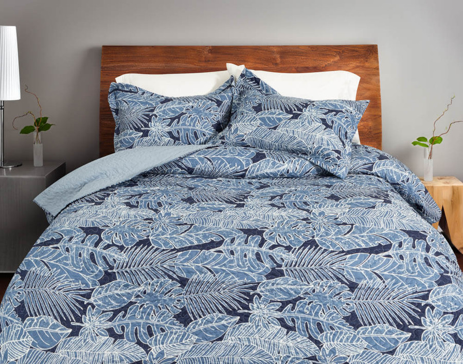 The Anup Coverlet Set features a blue botanical print of various tropical leaves.
