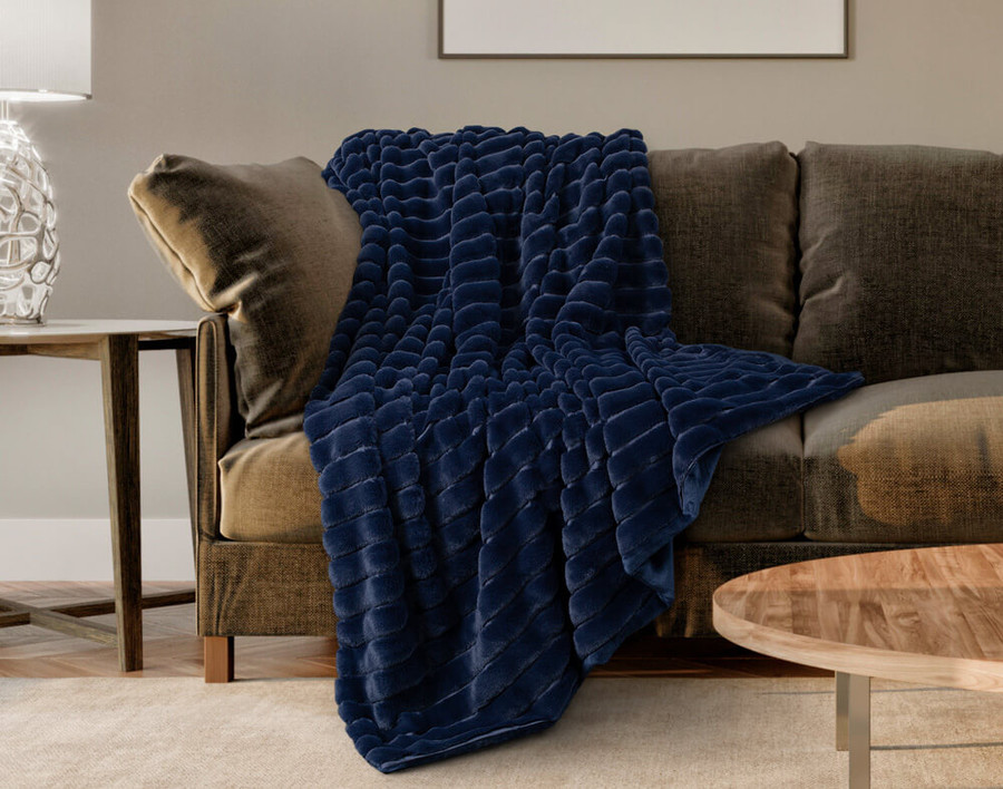 The Ribbed Faux Fur Throw in Midnight, a deep navy blue, draped across a couch.