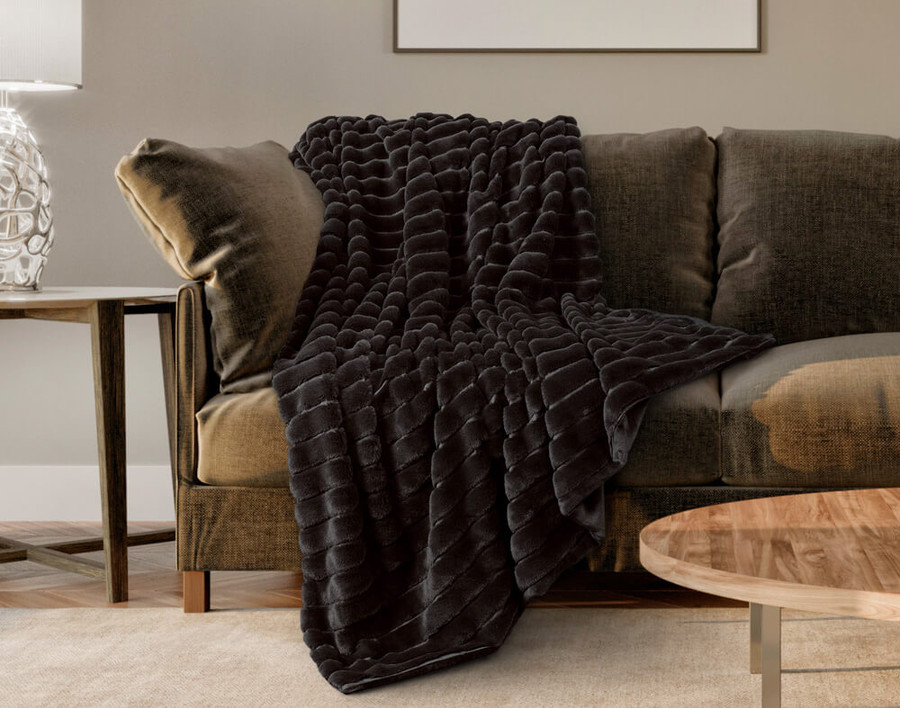 The Ribbed Faux Fur Throw in Onyx, a rich black, draped across a couch.