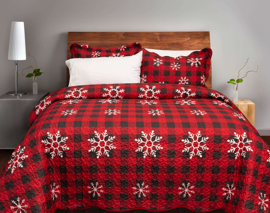 The Snowflakes Coverlet Set, featuring white snowflakes on a classic red and black plaid print.