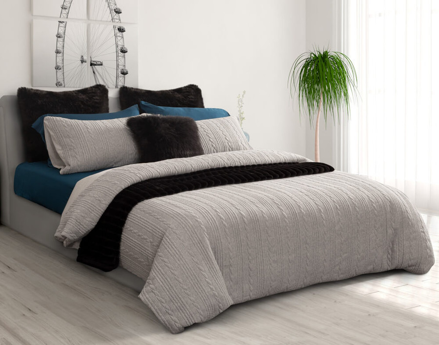 Side angle view of the Estevan Duvet Cover Set featuring a cable knit in a heathered grey, styled.