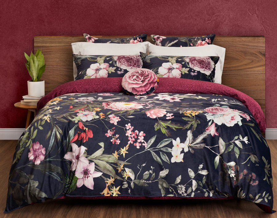 Monika Bedding Collection featuring romantic pink and purple florals on a dark blue background in a red room.