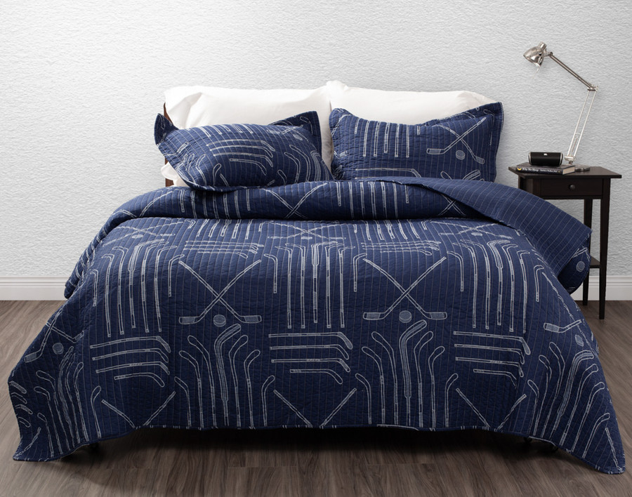 Hockey Sticks Cotton Quilt Set features white hockey stick outlines on a rich blue background.