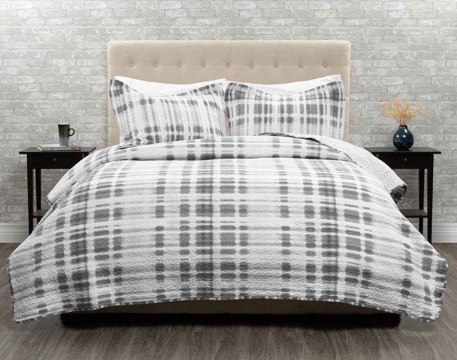 Novara Cotton Quilt Set features dark grey Shibori tie-dye design, on white background.