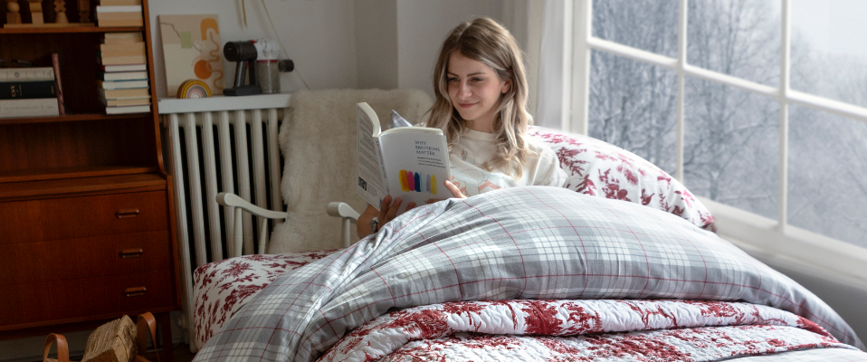Woman reading about Holiday Gift Ideas under a comfortable quilt in bed.