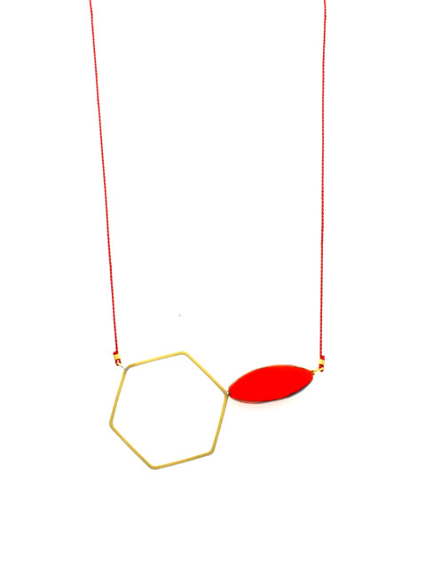 BRASS HEXAGON AND RED GLASS ON RED SILK
