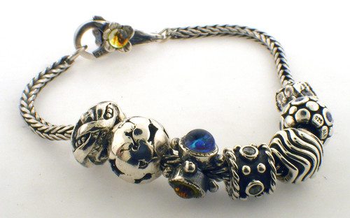 Sterling silver pandora style bracelet weighing 32.5 grams. 7.5 inches