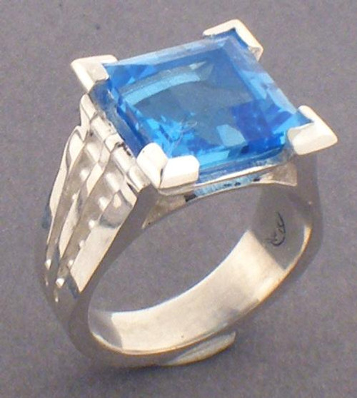This is a sterling silver and princess cut London blue topaz ring with decorative sides.  The London Blue Topaz is 10 x 10mm in size.  The ring weighs 11.0 grams and is a ring size 6.5