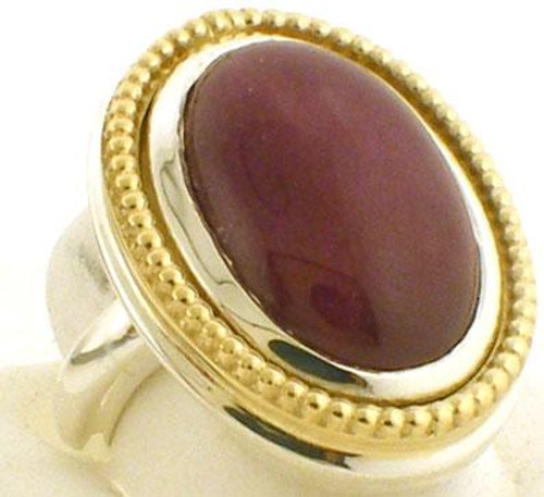 This is a large (27 x 21mm) two tone reconstituted ruby custom made ring.  Ring is sterling silver with a gold beaded frame. Ring is a size 7 and weighs 27.8 grams.
