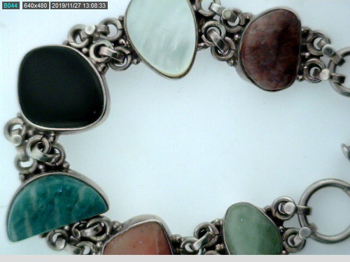 This is a silver bracelet with assorted stones. The total length of the bracelet is 7 inches.