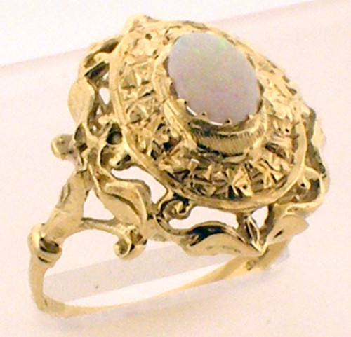 This is a 14 karat yellow gold ring with an opal center stone. The rings TW is 4.3 grams and is for a finger size of 7.
