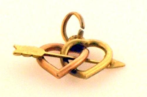 This is a 14 karat yellow and pink gold double heart charm with an arrow through it. The total weight of the piece is 1.3 grams.