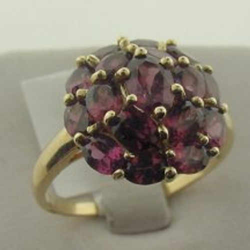 This is a 10 karat yellow gold ring with a rhodalite cluster. The rhodalite TW is 4ct and the ring's total weight is 3.8 grams. The ring was made for a finger size of 10
